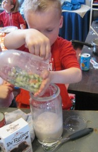 Afbeelding 2. Een kleuter speelt kokje en ontdekt allerlei zaken in verband met uitgieten en overgieten. Met dank aan Tonny Sijm die deze foto als voorbeeld liet zien bij haar voordracht 'Nu is het genoeg!' tijdens de oprichting Werkgroep Kleuteronderwijs op 25 april 2012.