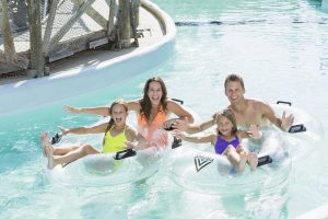 Family with two children (8 and 9 years) on lazy river at water park.